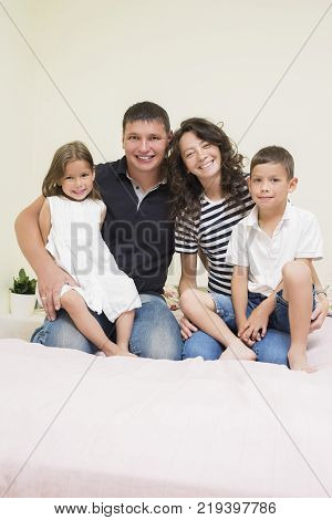 Family Ideas. Happy caucasian Family of Two Parent and Two Kids Sitting Together Embraced and Smiling Happily. Vertical Image Composition