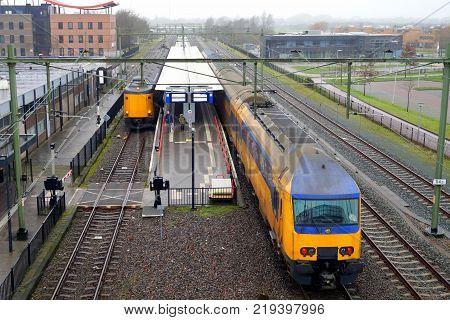 Steenwijk, The Netherlands - December 23, 2017: Yellow Dutch Railway double deck train entering Steenwijk railway station on a foggy day.