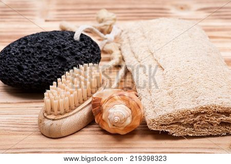 Natural bristle hand and nail wooden brush, volcanic pumice stone, loofah sponge and shell on wooden vintage background