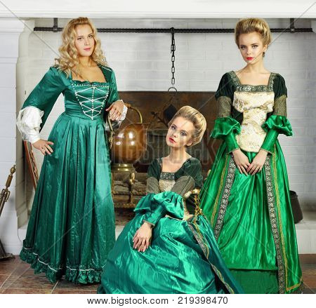 Collage with three beautiful young woman (two models) in green medieval costume stands near chimney with boiler