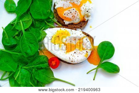 Tasty poached eggs on the bread with fresh green baby spinach on the white plate, healthy dietary breakfast, food border, delicious organic nutrition