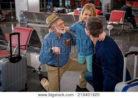 Closest relatives. Top view of cheerful aged man and his adult son are squatting while hugging their little child at airport lounge. They are feeling gladness while looking at each other with joy