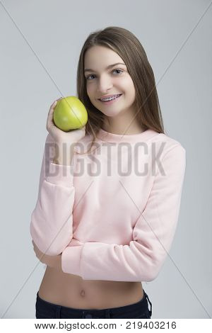 Dental Concepts. Portrait of Happy Teenage Female With Teeth Brackets. Posing With Green Apple and Smiling Against White.Vertical Image
