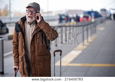 Deeply involved in conversation. Portrait of joyful senior man with beard is resting on walking stick and talking on smartphone with smile. He is standing outdoors with his suitcase. Copy space
