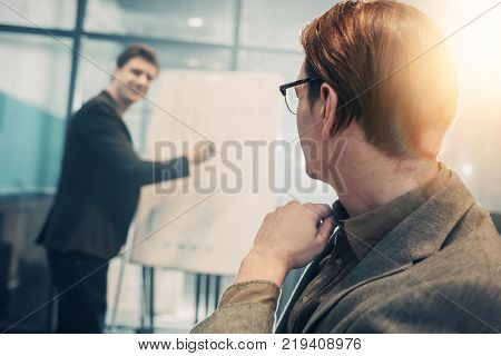 Male looking at partner while turning back to camera. Happy affiliate showing presentation. Business and job concept