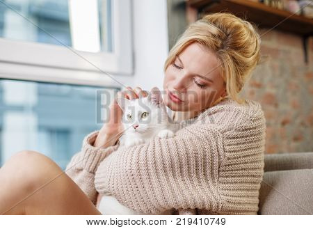 Peaceful female relaxing on couch near window and stroking fluffy cat. She is looking at animal