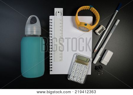 Close up of school supplies on black background in studio. Student table with basic and classic school supplies. Set of school supplies concept.