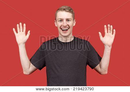 joyful happy young man raises his hands in the posture of