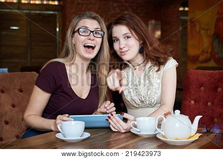 portrait of two stylish young girls over a table in a cafe discussing and splenocolic and shows her finger at someone with a laughing expression. The concept of ridicule fun abuse.