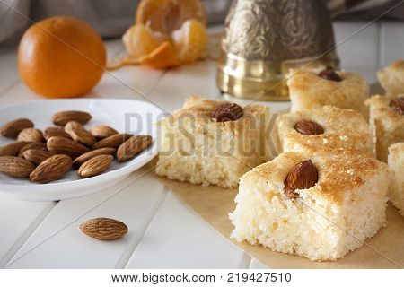 Still life Pieces Basbousa (namoora) traditional arabic semolina cake with almond nut and syrup, orange and cooper jezva. Copy space. Selective focus.