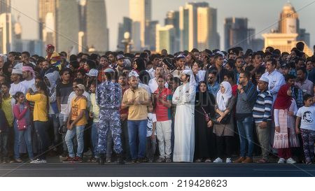 Doha, Qatar - December 18, 2017: A crowd of people watching perform of military and civil machines on Qatar National Day parade on the Corniche street, Doha, Qatar