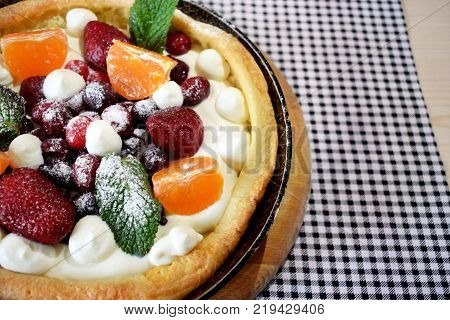 Danish pancake with berries and whipped cream topping covered with sugar powder