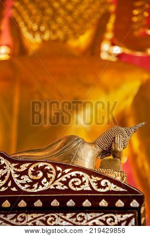 STILL LIFE OF RECLINING BUDDHA STATUE. Bronze Buddha statue in reclining posture with right hand supporting the head, lying on a rosewood bed with pearl inlay. In front, there is another Buddha statue out of focus.
