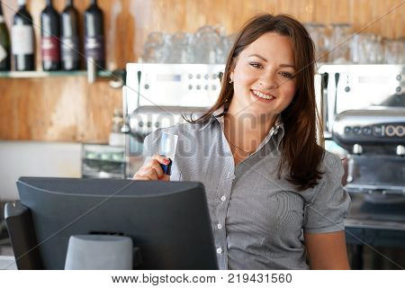 A restaurant worker registrating new order by cash-register