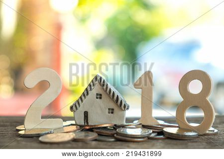 2018 New year concepts,Number two one eight put on coins,Model house replaced by zero.All laid on wooden floor,Light from the back.