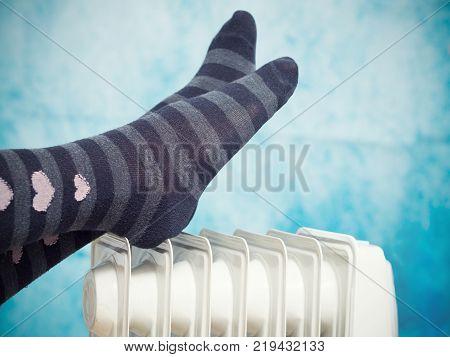 Female Feet Above The Heater.