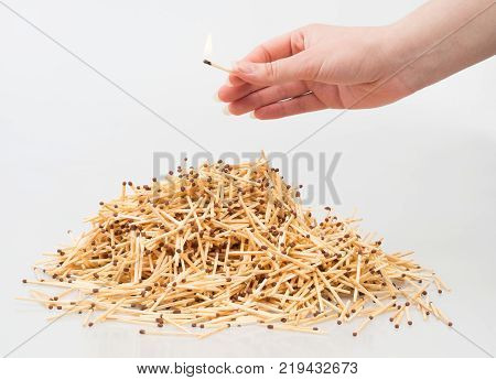 Bunch of matches threatened by another match.. A bunch of matches and a hand with a match