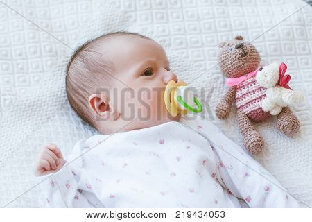 newborn baby laying on bed with his own toy bear. mother's treasure. beginning of life