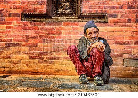 KATHMANDU, NEPAL - OCTOBER 21, 2015 : Old beggar in the street of Kathmandu