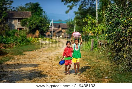 CHITWAN, NEPAL - OCTOBER 24, 2015 : Two nepalese children walking in their village