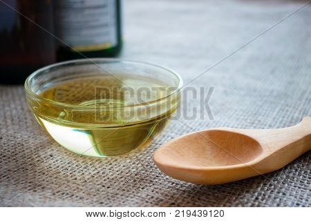 Liquid coconut MCT oil in round glass bowl with wooden spoon and bottles. Health Benefits of MCT Oil. Triglycerides a form of saturated fatty acid.