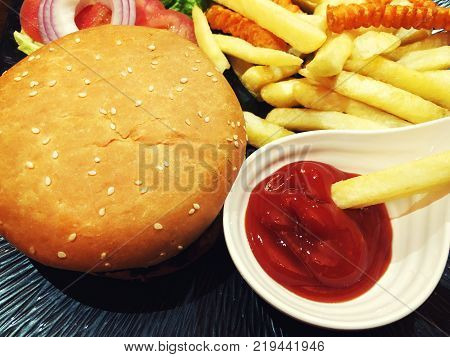 Hamburger on wooden table on a black plate. Fastfood meal. Delicious and gourmet hamburger.