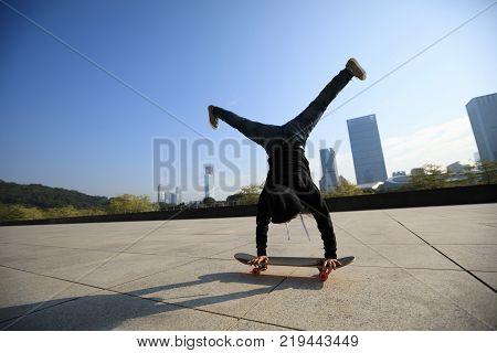 female skateboarder doing a handstand on skateboard in city