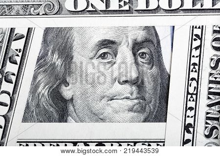 Benjamin Franklin on the one hundred dollar bill framed by other banknotes.