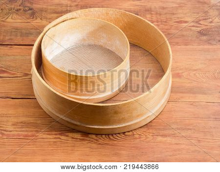 Two old round sieves different sizes with wooden frames and plastic mesh on an old rustic wooden table