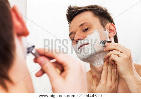 Handsome 30 years old man shaves in front of the mirror with adjustable Double edged safety razor