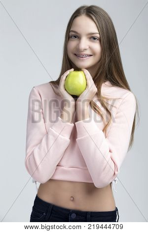 Dental Concepts. Portrait of Happy Teenage Female With Teeth Brackets. Posing With Green Apple and Smiling Against White.Vertical Image Composition