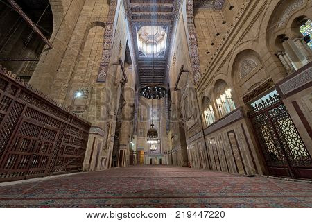 Cairo Egypt - December 16 2017: Interior of al Refai mosque with old decorated bricks stone wall colored marble decorations wooden ornate ceiling big brass chandeliers and wooden latticework door