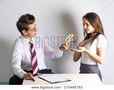 The concept of gratitude. Young handsome man giving money to a beautiful governess. Gray background.