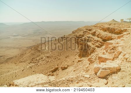 Negev desert landscape with yellow stones and mountain. Outdoor scenic view on sand, rocks and sky