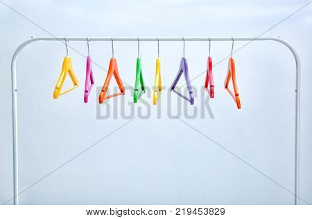 Wardrobe stand with hangers on light background