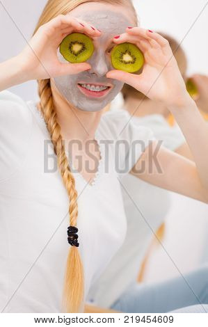 Facial dry skin and body care complexion treatment at home concept. Happy young woman having grey mud mask on her face holding kiwi piece on eyes