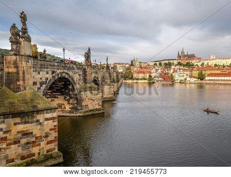 Prague, Czech Republic - October 13, 2017: Dramatic cloudy autumn view of Charles Bridge, Vltava river, St. Vitus Cathedral, Prague Castle and Old Town, Prague, Czech Republic.