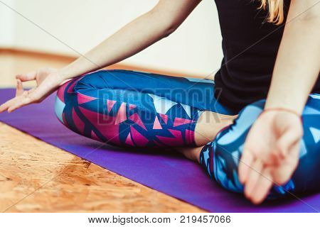Girl meditates in the Lotus position in the yoga room