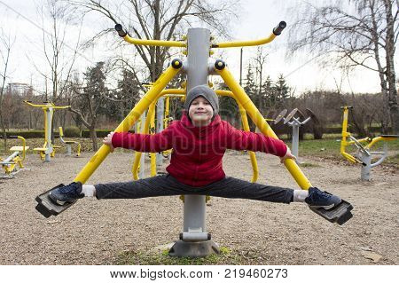 Active small boy 7 years old wearing a red jacket doing  sport exercises on a sport athletic playground outdoor in city park at late autumn. Cute boy in split outdoor like Van Damme. Concept of sport.