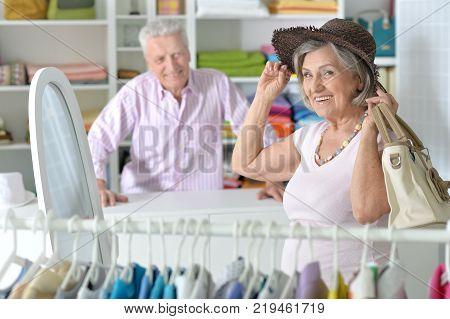 Portrait of senior couple choosing hat in shop