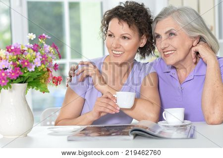 Portrait of a mother and daughter reading magazine, smiling
