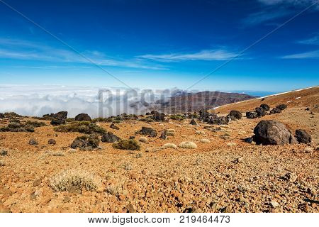 Teide National Park, Tenerife, Canary Islands - colourful soil of the Montana Blanca volcanic ascent trail to the 3718 m Teide peak. The Teide astronomical observatory can be seen in the distance.