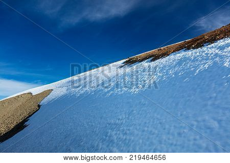 Winter panorama, snow-capped hillside in sunshine under a cloudy, deep-blue sky. An ideal scenario for all winter sports, in particular skiing