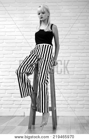 Monochrome vertical full length portrait of a young female fashion model posing gracefully sitting on a high stool looking to the camera femininity sensuality confidence.