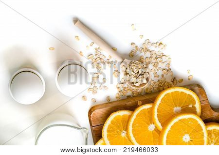 Oat Flakes Plate With Milk, Orange, Eggs On A Wooden White Table. Top View Of Healthy Oat Flakes Bre