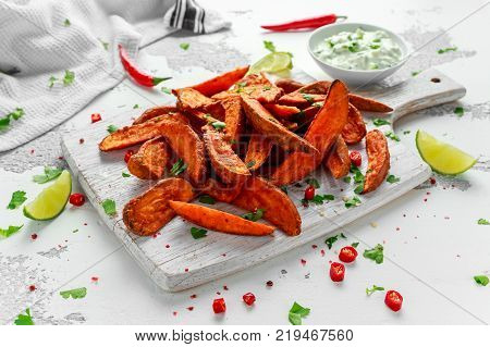 Healthy Homemade Baked Orange Sweet Potato wedges with fresh cream dip sauce, herbs, salt and pepper
