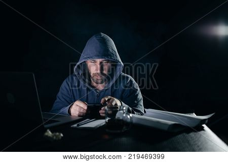 a mysterious man in a hood doing something illegal in a smartphone, a hacker