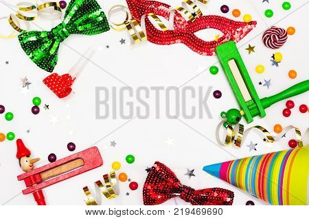 Festive party, carnival or Purim holiday background. Bright hats, masks and confetti on white background. Copy space