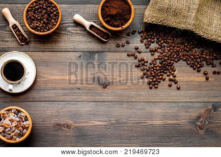 Coffee concept. Roasted beans, ground coffee, cup of espresso and sugar on dark wooden background top view.