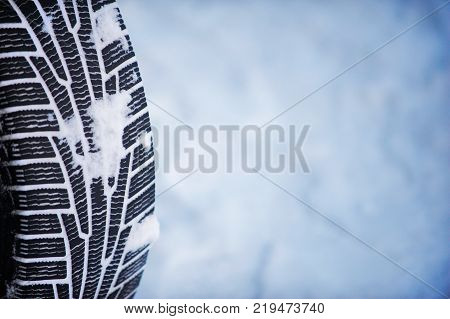 Closeup of car tire in winter on the road covered with snow